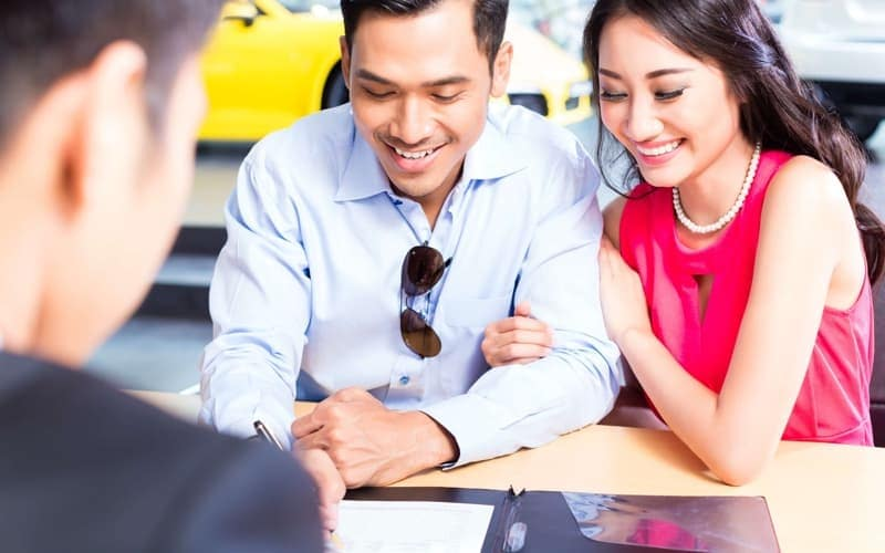 couple signing contract at car dealership