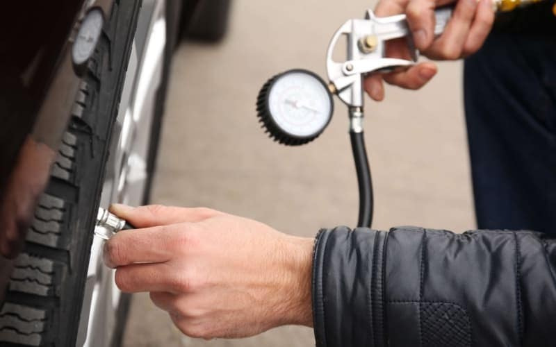 Auto mechanic checking tire pressure