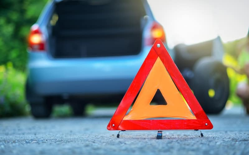 red warning triangle behind vehicle with a flat tire