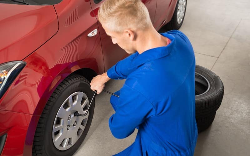 Mechanic Changing Tire In Garage