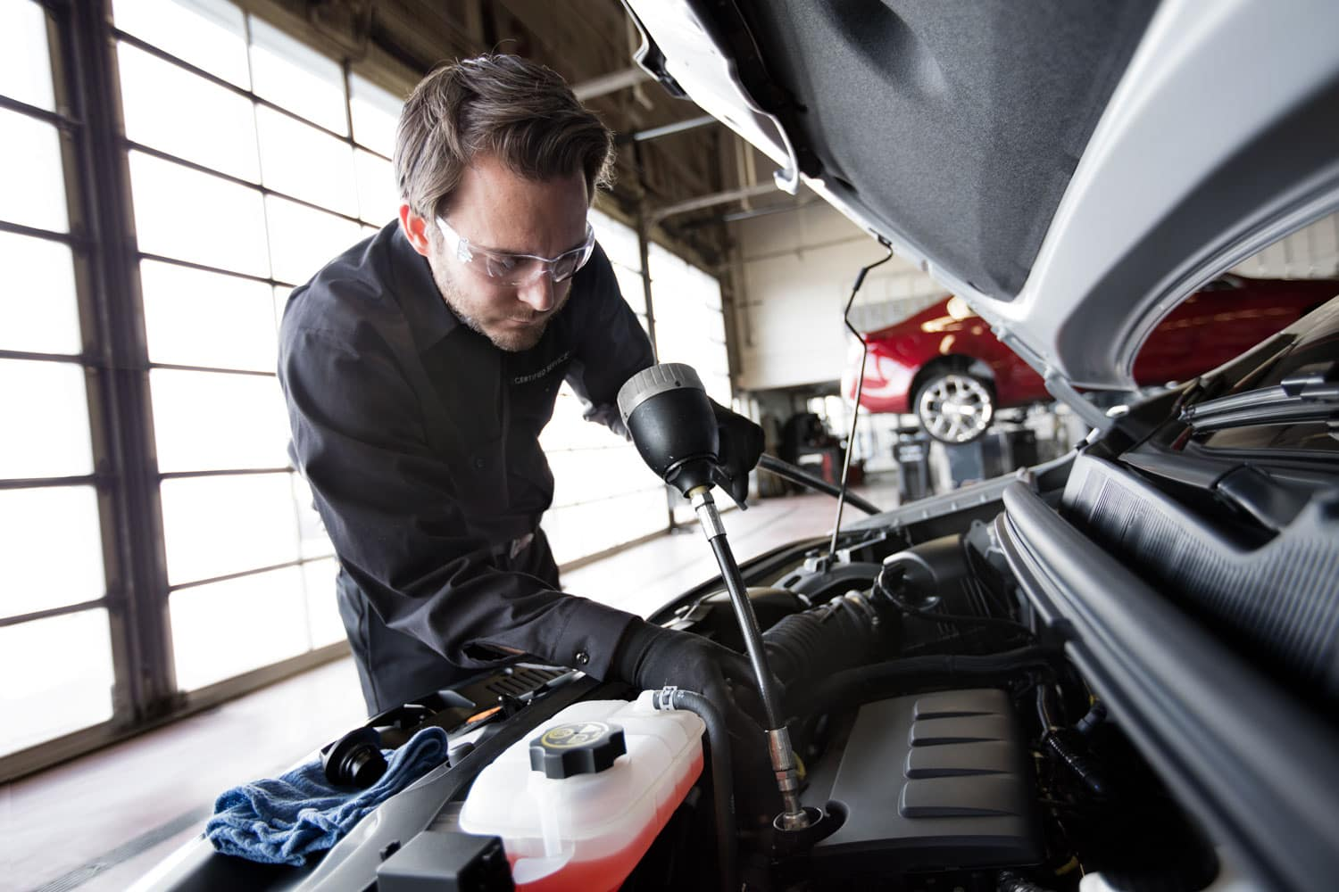 man working on SUV in Service area