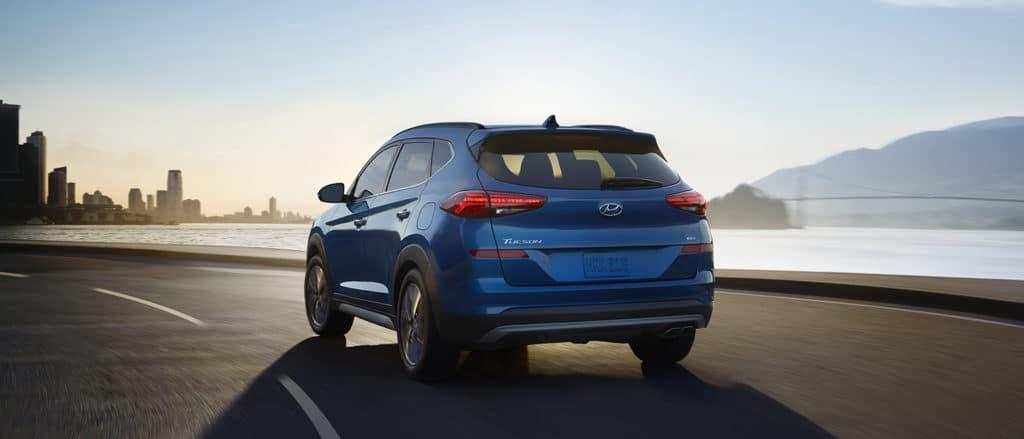 Washington Hyundai is a Hyundai Dealership in Washington near Bethel Park PA | Blue 2020 Hyundai Tucson driving on city road at sunset