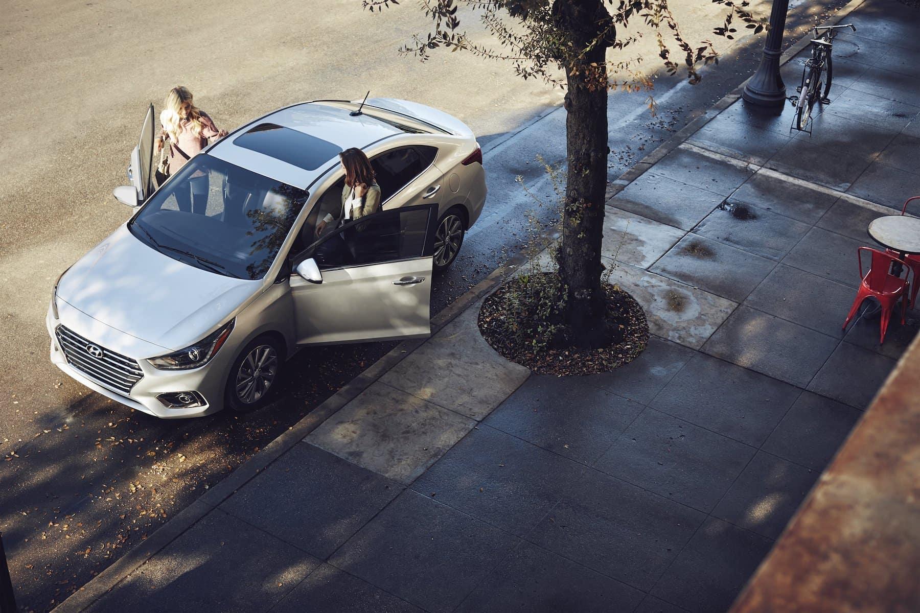 Washington Hyundai is a Hyundai Dealership in Washington near McGovern, PA | People getting out of 2020 Hyundai Accent on sidewalk