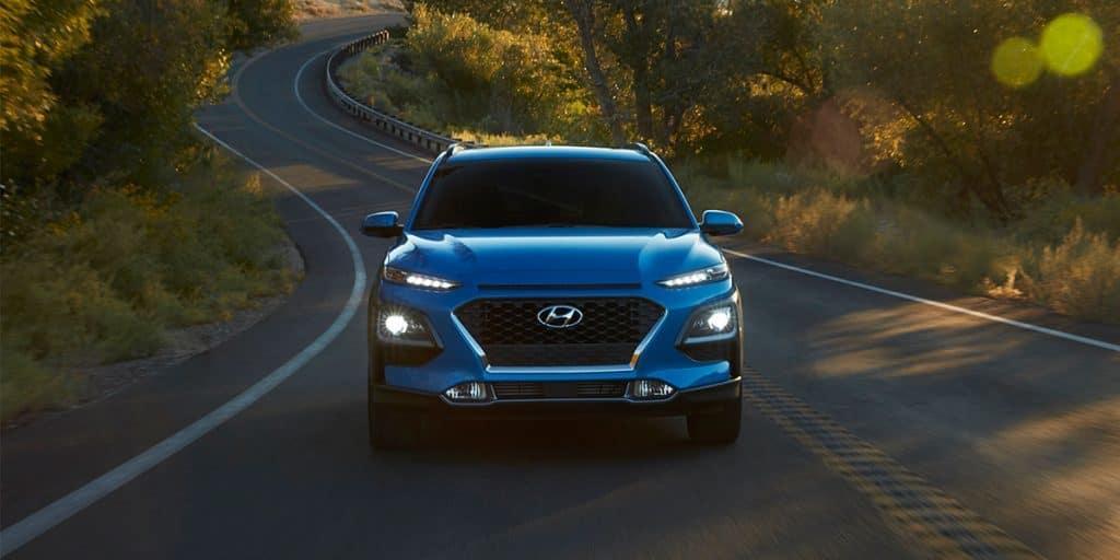 Washington Hyundai is a Hyundai Dealership in Washington near Canonsburg PA   Blue 2020 Kona Driving Down Country Road at Sunset