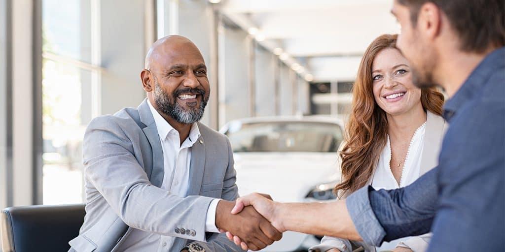 Washington Hyundai is a Hyundai Dealership in Washington near Arden, PA   Customer and Sales Advisor shaking hands with couple in dealership