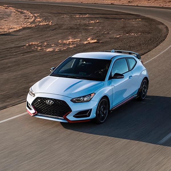 Benefits of Changing Your Hyundai's Oil at Washington Hyundai in Washington   Light Blue 2021 Veloster Driving Fast on Track
